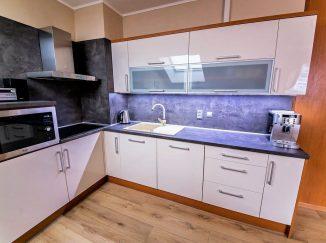Biela lesklá kuchyňa s drevo dekorom