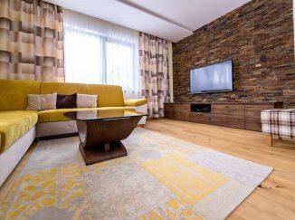 Obývačka so žltou sedačkou a dreveným nábytkom
