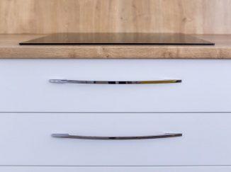 Detail varnej dosky a bielych kuchynských šuplíkov
