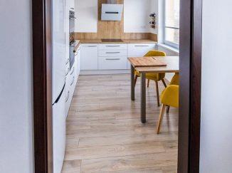 Pohľad do bielej modernej kuchyne s drevom