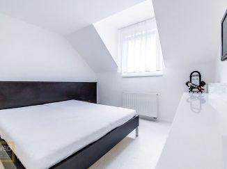 Čierna posteľ v bielej spálni