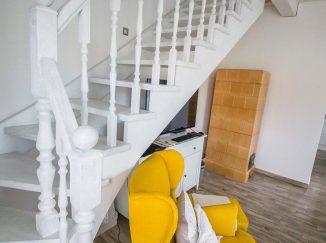 Biele interiérové schody so žltým kreslom