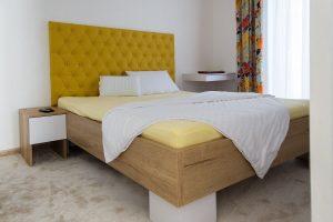Manželská posteľ so žltým čalúneným čelom