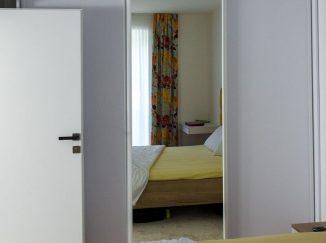 Biela vstavaná skriňa so zrkadlom v spálni