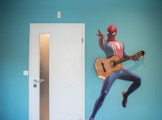 Spiderman na stene drží gitaru